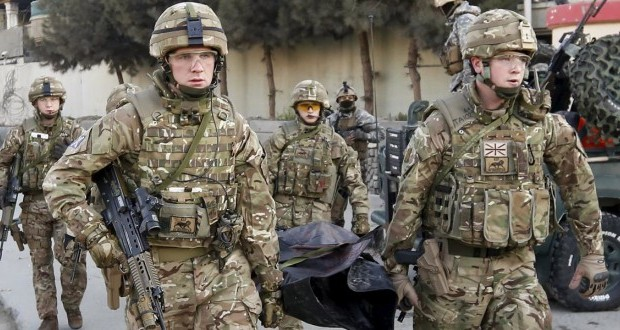 British soldiers carry the dead body of a victim after an attack on a guest house near the Spanish embassy in Kabul, Afghanistan December 12, 2015. Afghan security forces suppressed a suicide attack on a guest house attached to the Spanish embassy in Kabul, killing three Taliban fighters after hours of intermittent gunfire and explosions that lasted into the early hours of Saturday. REUTERS/Mohammad Ismail