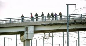 المهاجرين واللاجئين يقف على جسر بالقرب من موقع النفق في فريثون، باد كاليه قرب كاليه (ا ف ب)