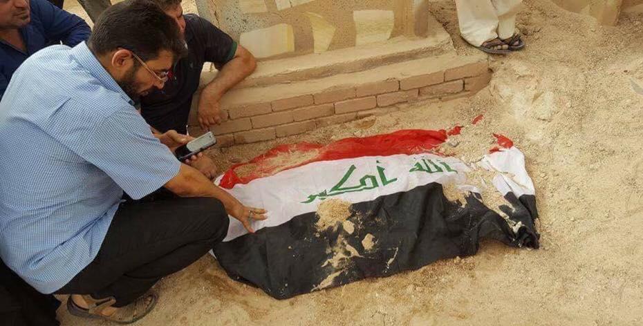 اللاعب الدولي السابق غانم عريبي بجوار قبر نجله الشهيد، اثناء مراسيم الدفن (3/تموز/2016 الاحد)