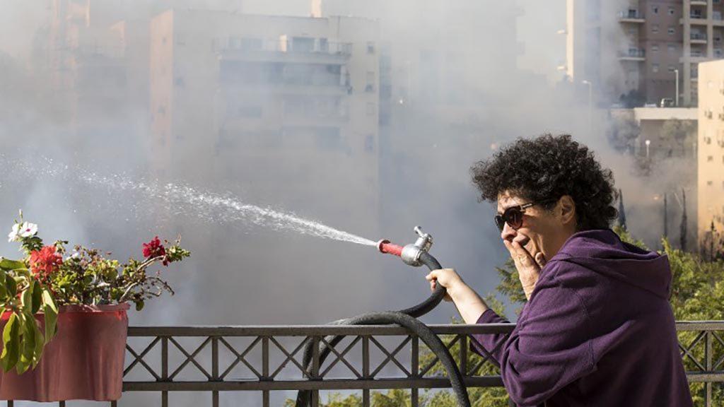 تحاول امرأة إسرائيلية لإطفاء الحريق بخرطوم من سطح مبنى في ميناء حيفا بشمال إسرائيل في 24 نوفمبر 2016 (AFP PHOTO JACK GUEZ)