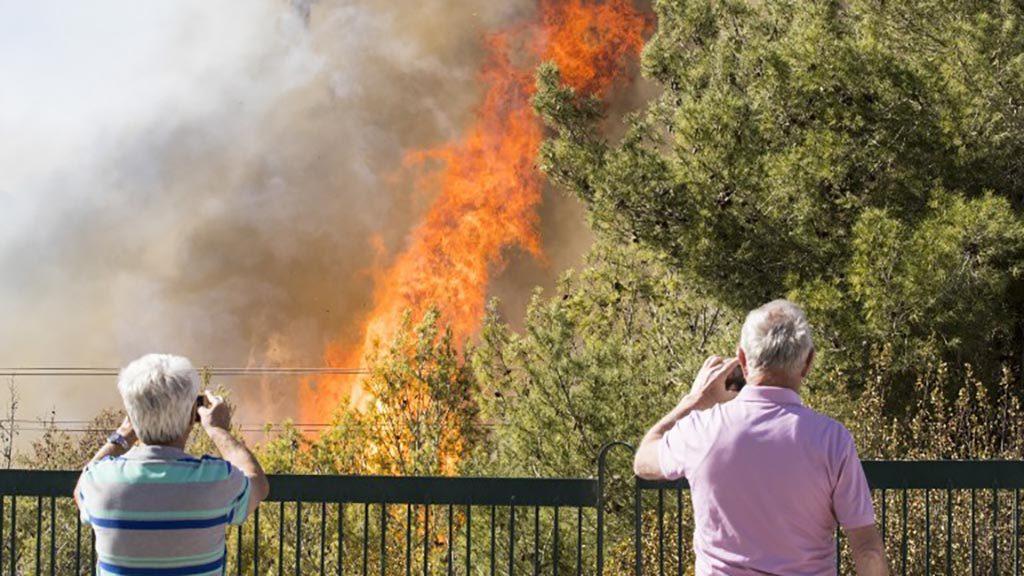 اثنين من الاسرائيليين التقاط الصور مع الهواتف المحمولة الخاصة بهم من الدخان ترتفع من حرائق الغابات في ميناء حيفا بشمال إسرائيل في 24 نوفمبر 2016 AFP PHOTO / Jack GUEZ