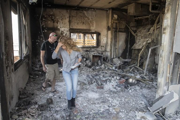 ريلي (R) وايال جولان تفقد الاضرار في منزلهم، الذي أحرق خلال الهشيم الناجمة عن الظروف الجافة، في 23 نوفمبر 2016 في بلدة بشمال اسرائيل زخرون يعقوب AFP PHOTO / JACK GUEZ