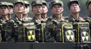 جنود كوريا الشمالية يتحولون ويتطلعون إلى زعيمهم كيم جونغ أون من مركبة موكب عسكري وهم يحملون عبوات تحمل الرمز النووي خلال احتفال بالذكرى الستين لهدنة الحرب الكورية في بيونغ يانغ، كوريا الشمالية، 27 يوليو / تموز 2013