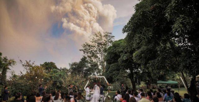 صور.. زفاف عروسين بالفلبين تحت سحابة من الرماد البركاني